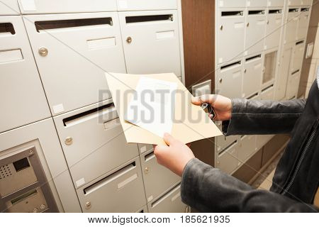 Close-up picture of woman's hands holding envelopes with copy-space next to mailboxes
