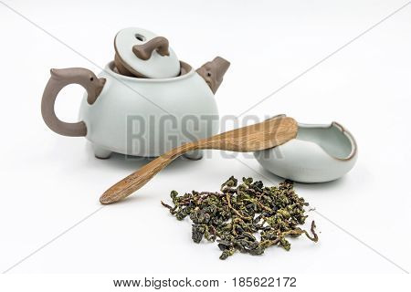 Chinese Oolong Green tea (Tie Guan Yin) with small pot, spoon and bowl isolated on white.