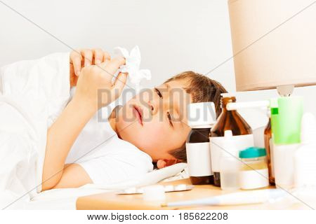 Five years old boy with bad cold laying in bed and using paper napkins