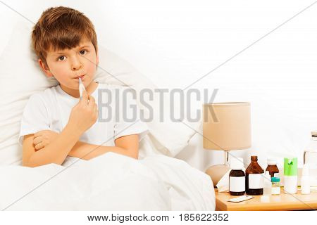 Sick boy sitting in bed and taking temperature against background with copy-space