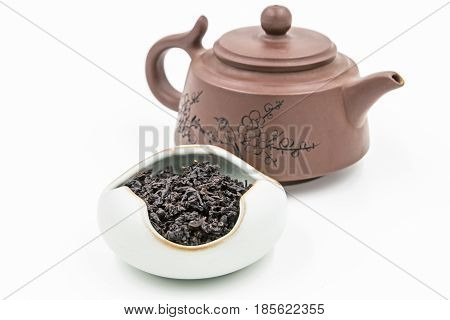 Chinese Oolong Dark Red tea (Black Tie Guan Yin) in a blue ceramic bowl with small pot isolated on white.