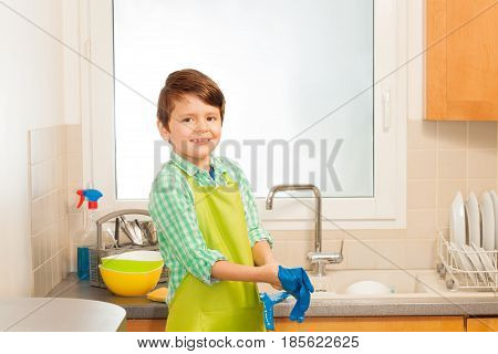 Portrait of happy six years old boy putting on blue rubber gloves and apron before dishwashing in the kitchen