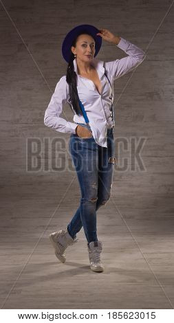 Adult Pretty Woman Dressed In Jeans, A White Blouse And Hat Posing On A Dark Background