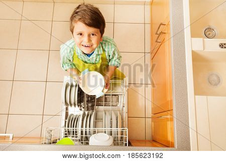Top view picture of happy kid boy taking out dishes from dishwasher in the kitchen
