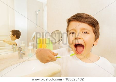 Portrait of cute boy with toothbrush at his hand and mouth wide opened in the bathroom