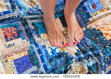 patchwork, stitching, handcraft, interior, home cosiness, beauty concept - two woman's feet with bright pink nail polish standing on aesthetic quilt made of textile squares with floral prints