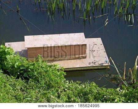 Floating otter survey board made from wood. To show the presence of otters and other mammals. Floating in a river with surrounding vegetation.