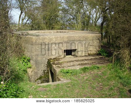 A World War Two concrete pillbox on the east coast of England. Shows the entrance an embrasure and a central anti aircraft gun well on top. Background of trees.