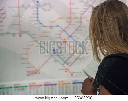 Back view of woman orientating herself on the public transport map. Search transport links on map urban transport