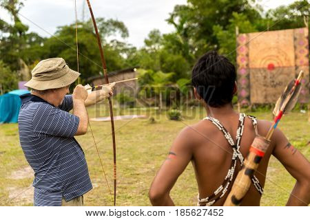 Tourist learning lessons with a man from Tupi Guarani tribe with bow and arrow, Brazil