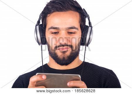 Cropped shot of a happy handsome beard young man listening to music and holding a cellphone guy wearing gray t-shirt and headphones isolated on white background