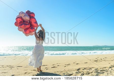 Young woman in white dress with red balloons on the beach, enjoying sunny windy day. rear view
