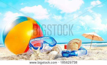 colorful beach ball, blue goggles on the sand with paper umbrella