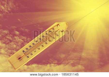 thermometer on wood plate sunshine background. Summer heat.