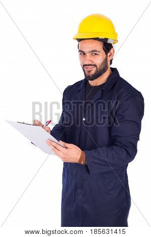Handsome beard young worker holding a clipboard and taking some notes guy wearing workwear and yellow helmet isolated on white background