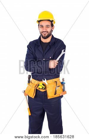Handsome beard young worker smiling and holding an english key guy wearing workwear and yellow helmet with belt equipment isolated on white background