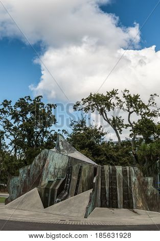 Auckland New Zealand - March 4 2017: Bronze metal statue also fountain in the courtyard of Holy Trinity Cathedral with green vegetation in back under blue cloudy sky.