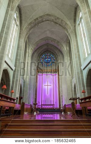 Auckland New Zealand - March 4 2017: Chancel at old part of Holy Trinity Cathedral features wooden benches and altar in front of purple lighted back with large cross. Towering ceiling.
