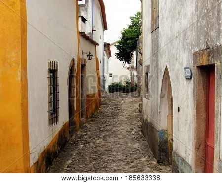 Obidos, Portugal. Beautiful narrow walled street. Obidos is an ancient medieval Portuguese village originated in the 11th century and still situated within the same castle walls.