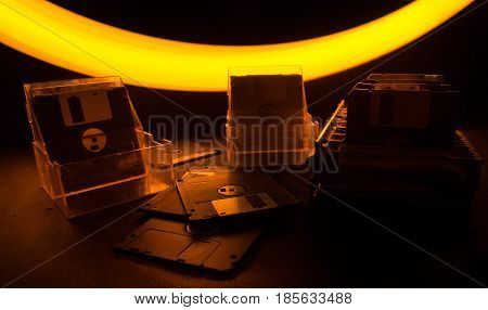 Pile Of Black Floppy Disks On Dark Background With Light. Vintage Computer Attributes