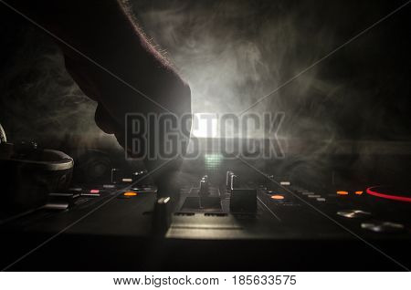 DJ Spinning Mixing and Scratching in a Night Club Hands of dj tweak various track controls on dj's deck strobe lights and fog selective focus close up