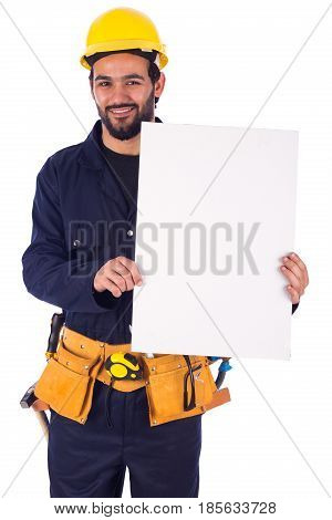 Handsome beard young worker smiling and holding a blankboard guy wearing workwear and yellow helmet with belt equipment isolated on white background