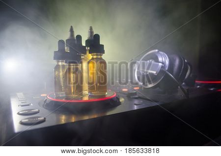 Vape And Dj Club Concept. Smoke Clouds And Vape Liquid Bottles On Dj Mixer Close Up. Light Effects.