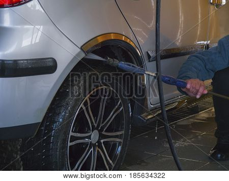 The worker washes the wheel of a car