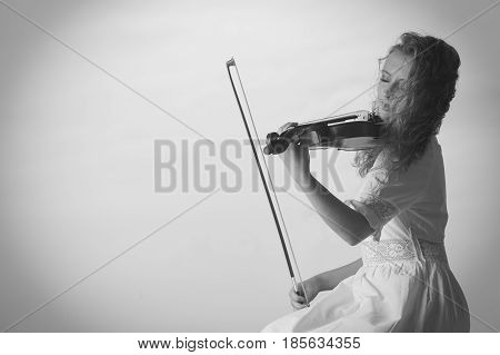 Classical music passion concept. Musician violinist woman playing on violin enjoying her hobby.