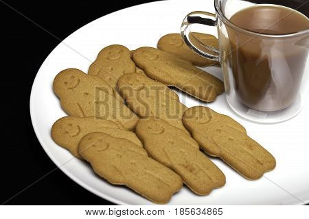 Afternoon snack comfort food. Gingerbread men biscuits and a cup of tea. Small ginger biscuits and tea in a see through mug on a white plate against a black background.