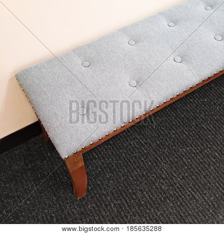 Detail of interior with gray elegant bench on carpet floor.