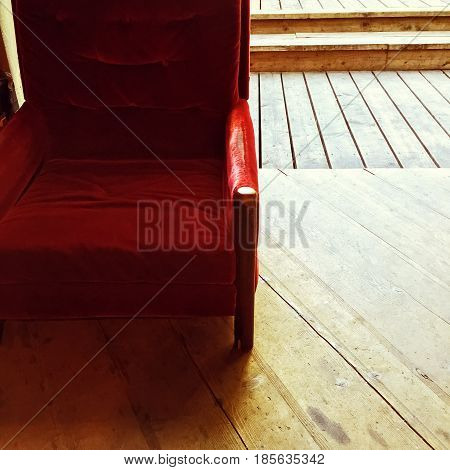 Rustic interior with vintage red velvet armchair and old wooden floor.