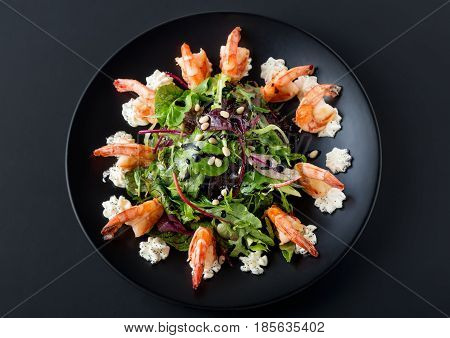 Tasty salad with tiger shrimps, lettuce, salad and philadelphia cheese on black plate. Top view and selective focus.