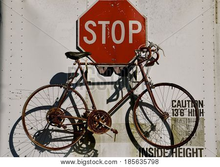 A wall display consists of an old vintage bicycle throwing it's  shadow and a stop sign.