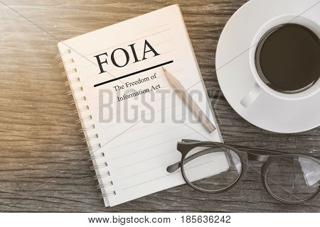 Concept FOIA (The Freedom of Information Act) message on notebook with glasses pencil and coffee cup on wooden table.