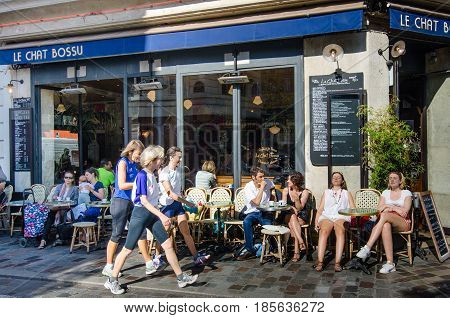 PARIS - FRANCE AUGUST 29, 2015: Parisians enjoy the warmth of the sun at an outdoor café while having their lunch.