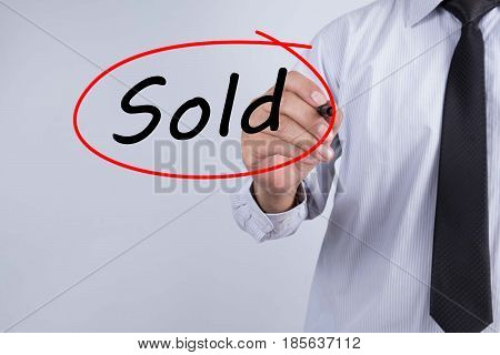Businessman Hand Writing Sold with a marker over transparent board Business concept.