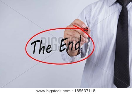Businessman Hand Writing The end. with a marker over transparent board Business concept.