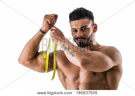 Muscular bodybuilder man measuring thigh with tape measure, close-up isolated on white background.