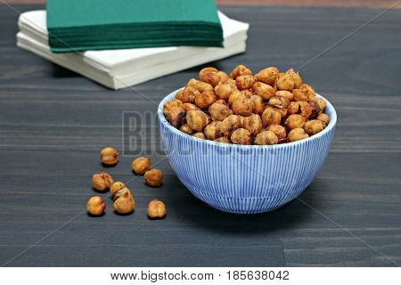 Roasted Chick Peas or Garbanzo beans in a blue striped bowl.  Close up with copy space.