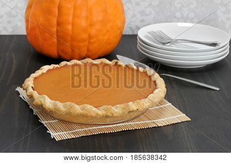 Whole homemade pumpkin pie with pumpkin in background.