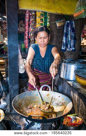 MINGUN, MYANMAR- MARCH 6, 2017: Burmese woman making food at street of Mingun on March 6, 2017, Myanmar. (Burma)