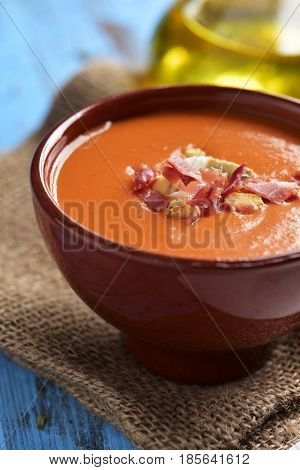 closeup of an earthenware bowl with spanish salmorejo cordobes or porra antequerana, a cold tomato soup topped with serrano ham and croutons, on a blue rustic table