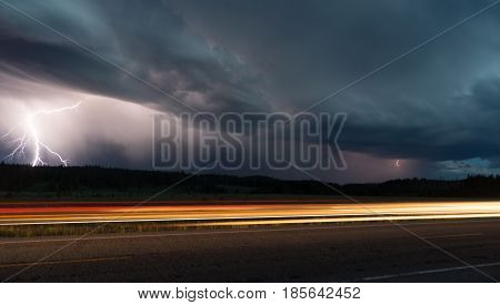 Two lightning bolts appear in this scene as a car passes in Yellowstone National Park
