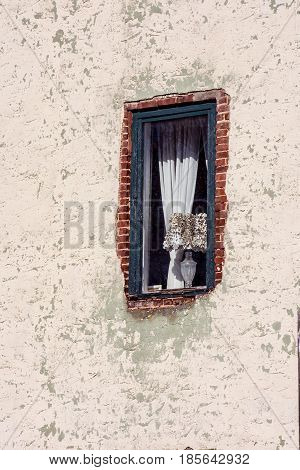 A historic building in Smithtown New Jersey with an old window with brick showing through.