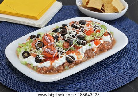 Mexican layered ground beef and refried bean dip. Decorated in a masculine manner with footballs for Dad.