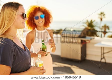 Two beautiful woman holding alcoholic ciders with smiles on their faces while standing on a rooftop at a barbecue with a stunning ocean view on a warm summers day.