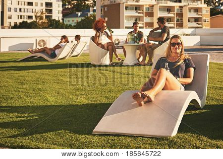 Beautiful young girl looking at the camera while lying down on a sun bed, holding an alcoholic beverage in her hand with a group of people socialising behind her in the background.