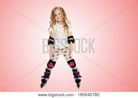 Beautiful, chubby little girl with long, blond, curly hair.Girl riding roller skates in protective gear.Pale pink gradient background.