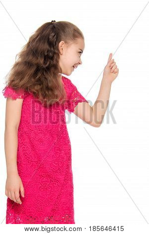 A beautiful little girl of primary school age, with long flowing hair, in a bright red dress.The girl is threatening someone with her index finger.Isolated on white background.